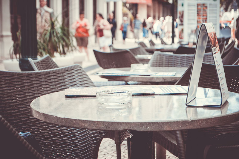 Empty chairs and tables arranged at sidewalk cafe