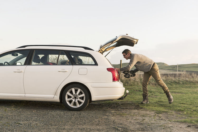 Side view of man standing on car against sky