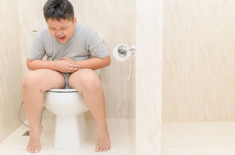 Boy with hands on stomach sitting in toilet