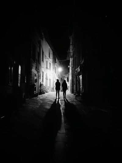 Rear view of silhouette people walking on alley amidst buildings in city