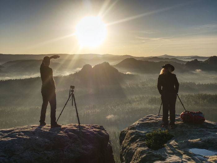 Two hikers taking pictures and talk on top of mountain. photographers with gear on top of mountain