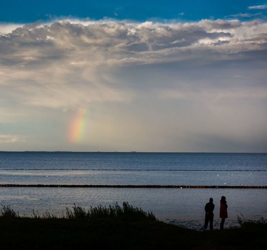 Man and woman standing by seascape against cloudy sky