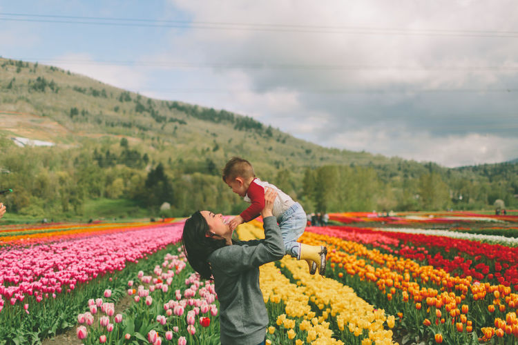 Side view of mother lifting son while standing by colorful flowering plants on field against sky
