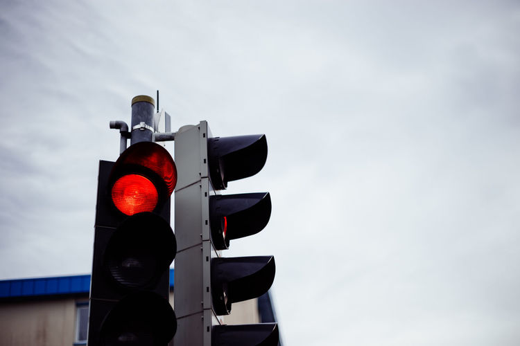 Low angle view of road signal against sky