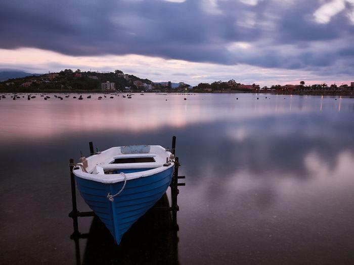 Sailboats moored in lake at sunset