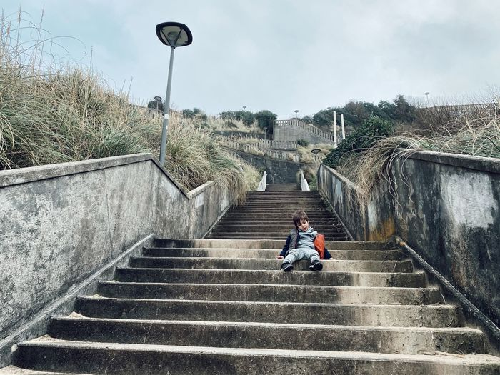 Man sitting on staircase against sky