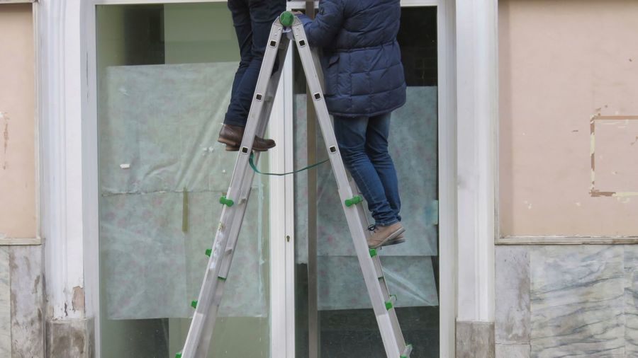 Low Section Of Men Climbing On Ladder
