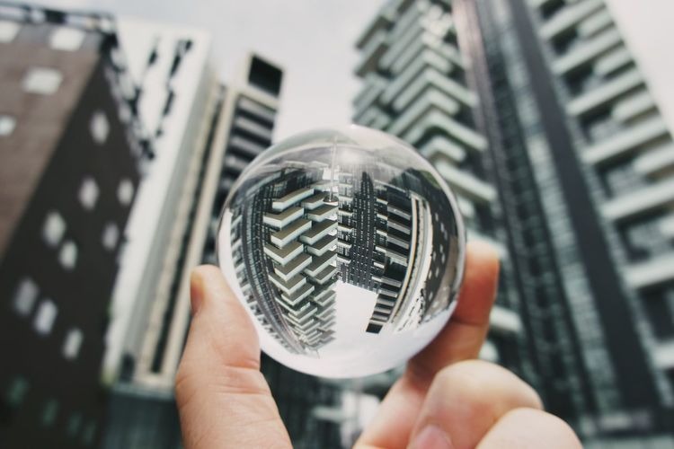 Close-up of person holding crystal ball against buildings
