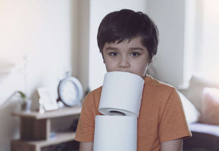 Portrait of boy holding toilet papers at home