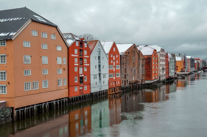 Residential buildings by canal against sky