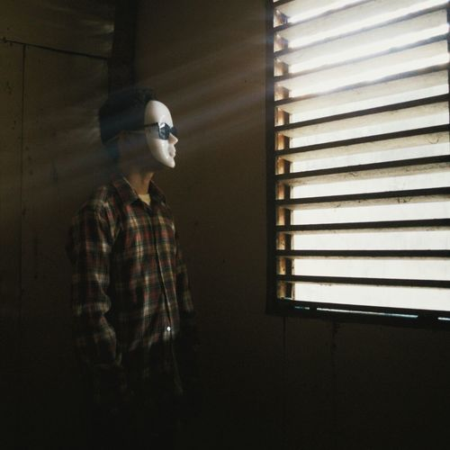 Man Wearing Mask Standing By Window
