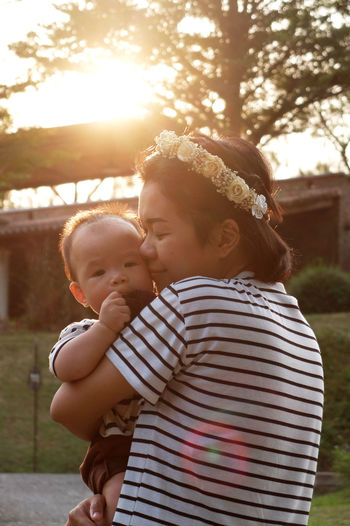 Mother Holding Baby At Sunset