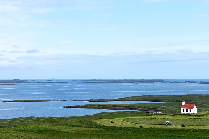 Ocean view with red roofed white church. Travel Iceland Water Sky Scenics - Nature Beauty In Nature Day Sea Nature Land Grass Cloud - Sky Tranquility Tranquil Scene No People Horizon Over Water Non-urban Scene Transportation Outdoors