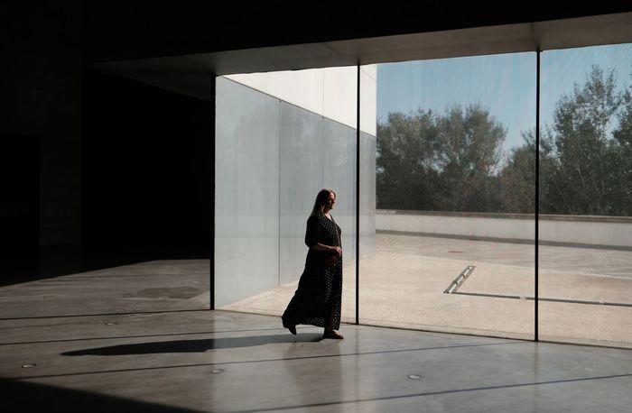 WOMAN WITH UMBRELLA WALKING ON FLOOR