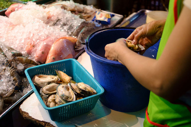 Midsection of vendor cleaning oysters at fish market