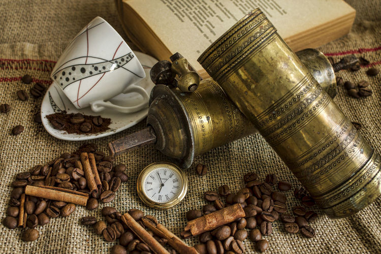 Close-up of roasted coffee beans with book and pocket watch on sack
