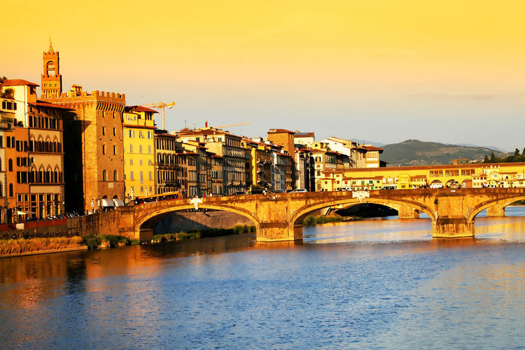 Arch bridges over arno river by buildings against sky