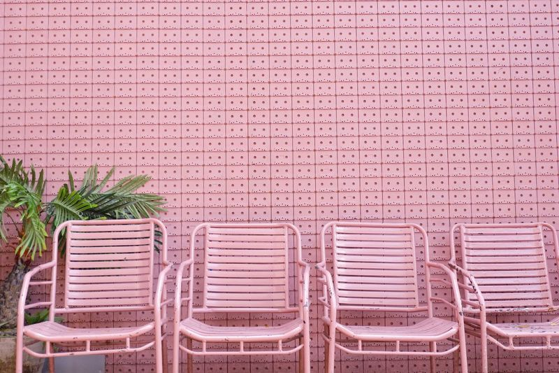 Empty Pink Chairs Arranging Against Wall