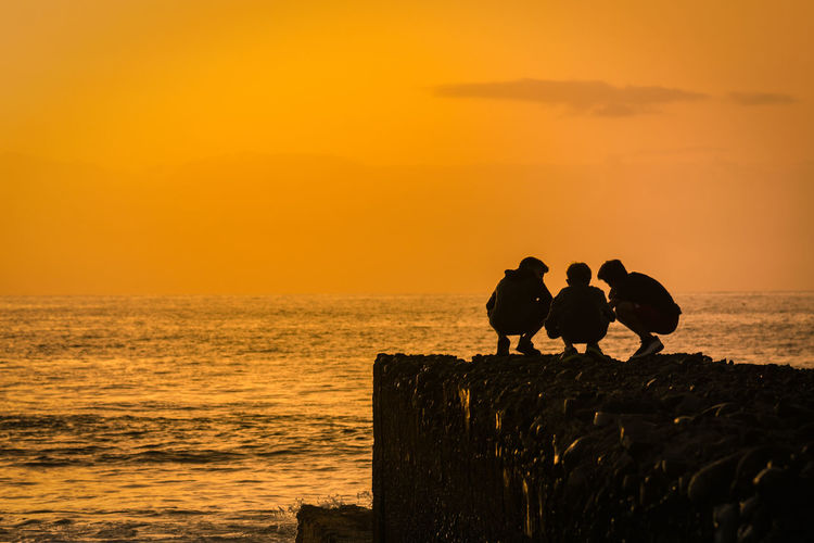 Silhouette of people crouching on rock by sea against sky during sunset