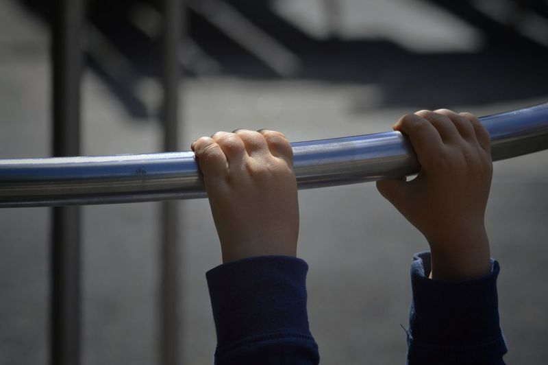 Cropped hands of child holding railing