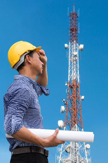 Low angle view of engineer standing against communications tower