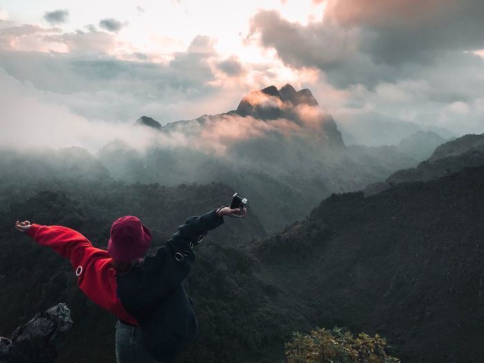 Rear View Of Woman With Arms Outstretched Looking At Mountains Against Cloudy Sky During Sunset