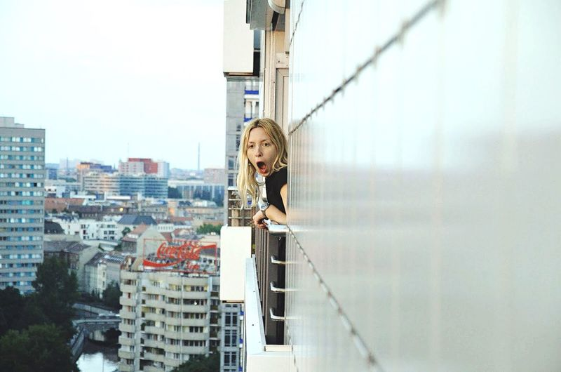 Portrait of young woman with cityscape in background