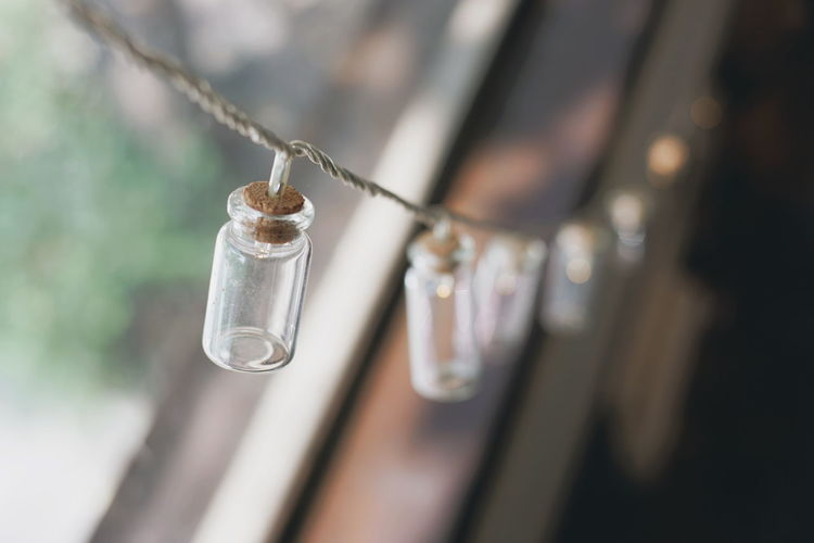 Close-up of bottles hanging on string