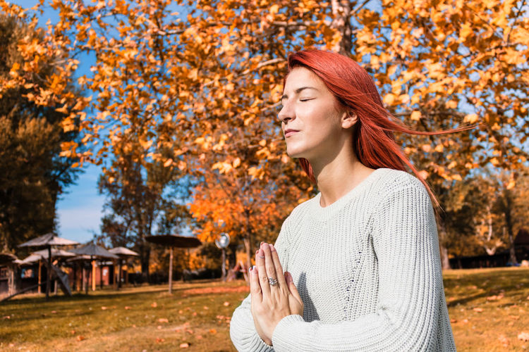 Young woman looking away while standing by tree during autumn
