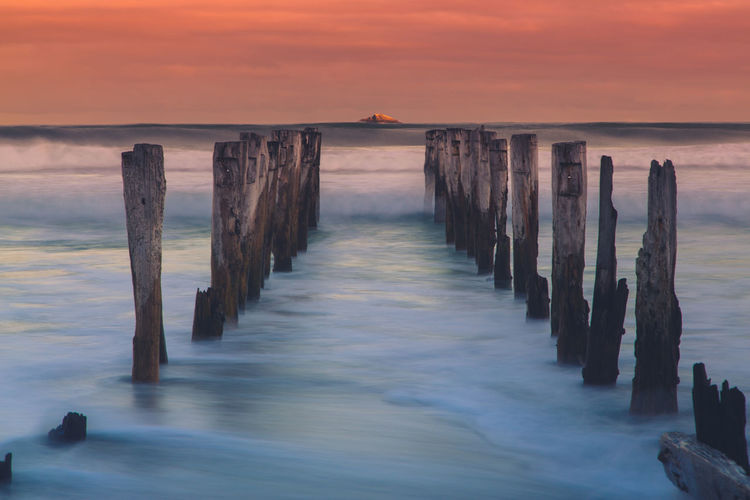Wooded Posts In Sea During Sunset
