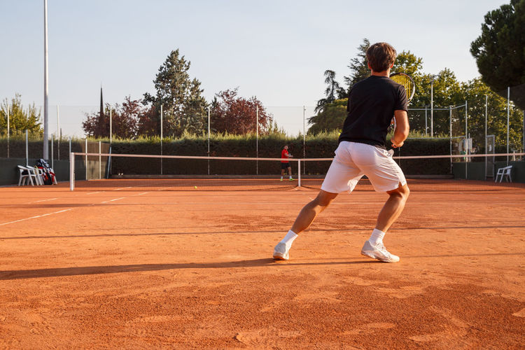Young Men Playing Tennis At Court