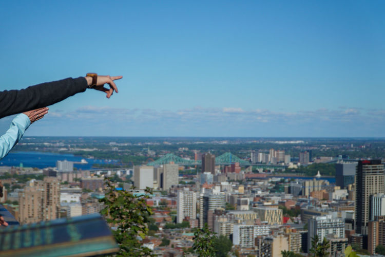 Hands pointing towards cityscape against blue sky
