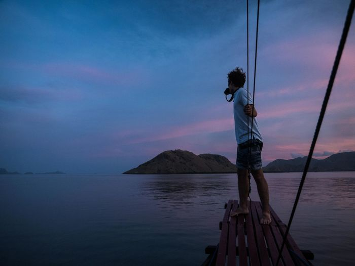 Full length of man photographing while standing on pier against sky during sunset