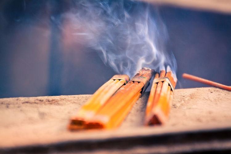 Close-Up Of Incense Sticks Burning On Railing