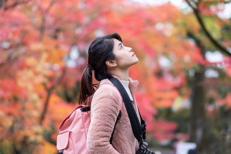 Woman looking away while standing against tree during autumn