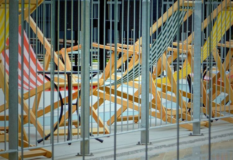 Deck chairs on sidewalk seen through fence