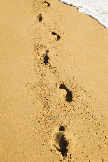 High angle view of footprints on sand at beach