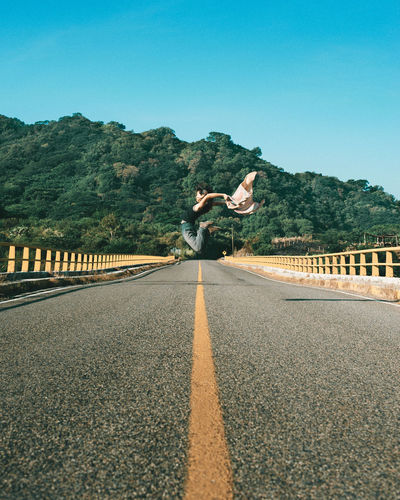 Woman jumping on road against clear sky