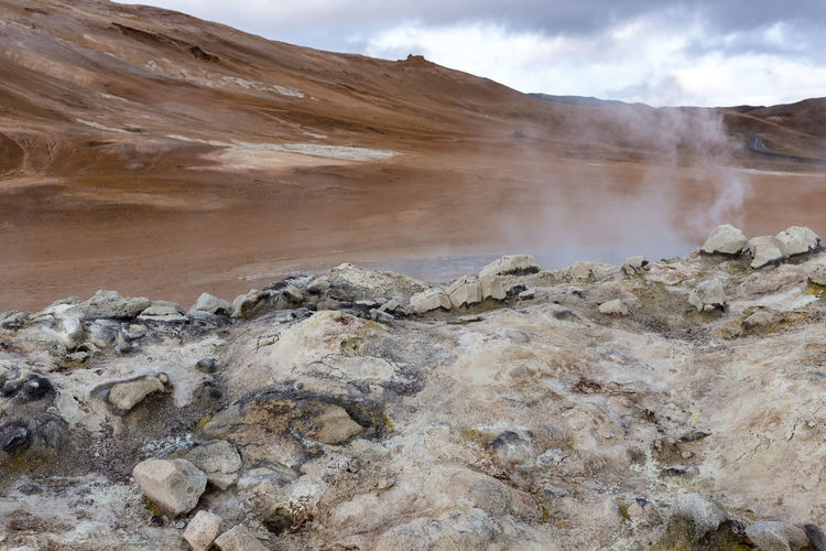 Hverir, front focus on bright rocks Interesting things sharp, civilization out of focus. That's how vacations should look like. Hot Hverarönd Mars Myvatn Steam Boiling Empty Geothermal  Grey Hverir Mud Orange Color Otherworldly Puddle Road Trip Rotten Egg Stink Sulfur