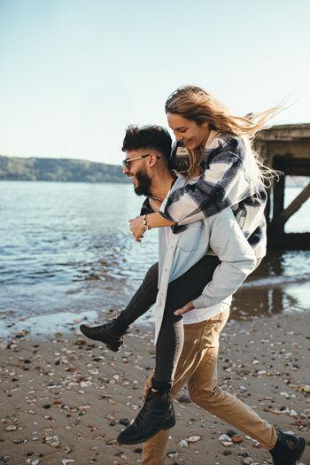 Full length of couple on beach against sky