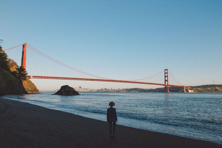 Woman standing on shore against golden gate bridge