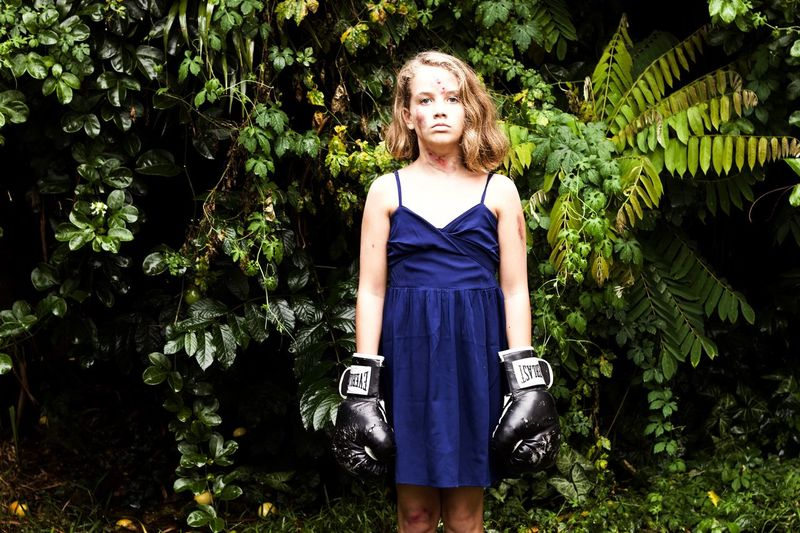 Boxer Battered A Force To Be Reckoned With. Strongwoman Rugged Beauty Still Standing Battle Ready Plant Tree Front View One Person Three Quarter Length Standing Real People Lifestyles Growth Portrait Young Women Outdoors