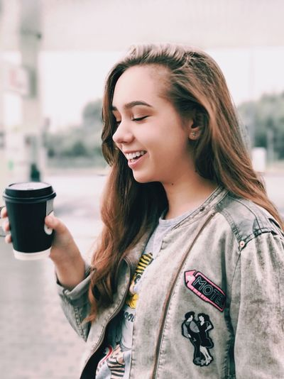 Portrait of smiling young woman holding coffee