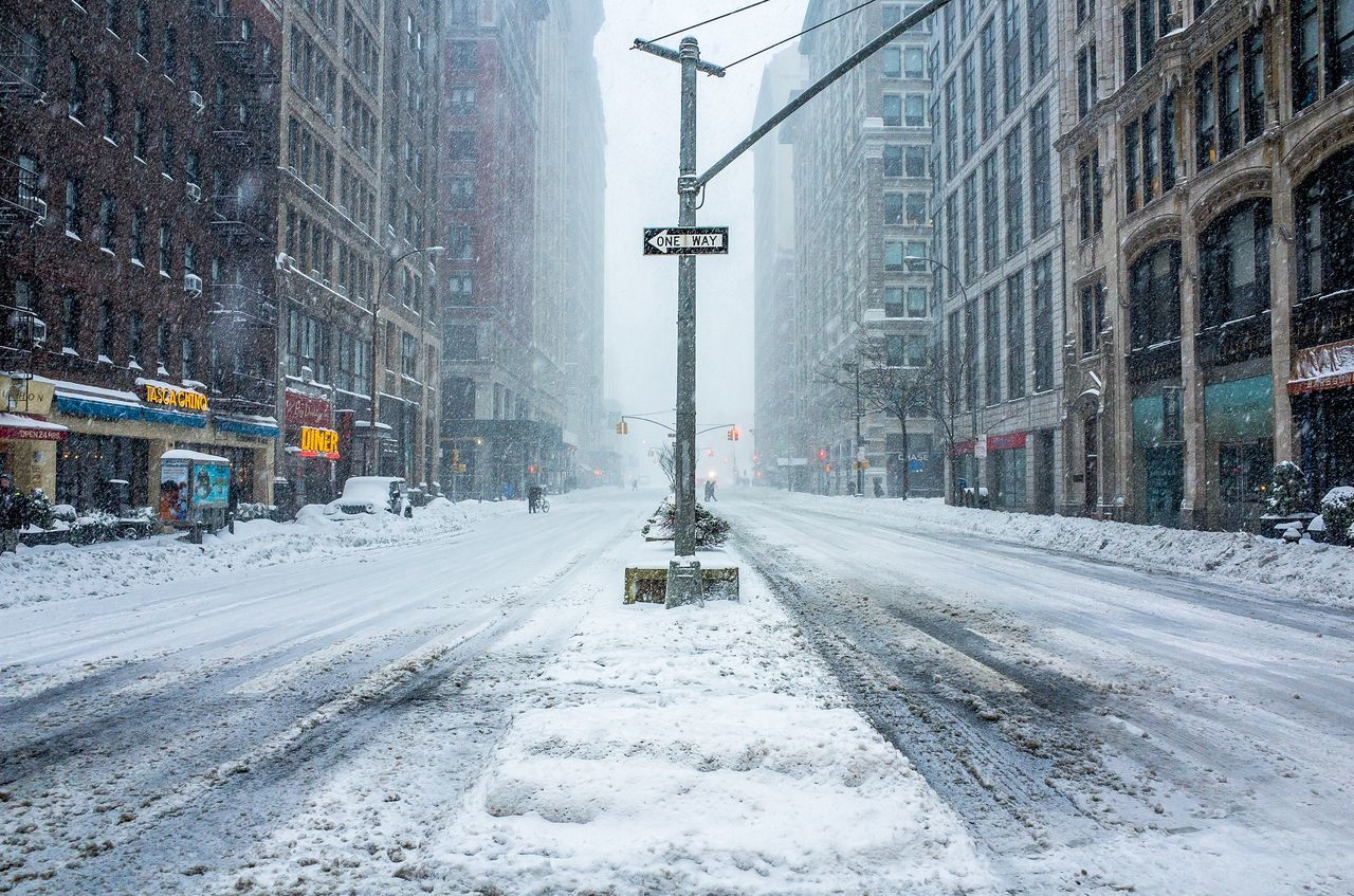 Street Covered With Snow Amidst Buildings In City During Snowfall