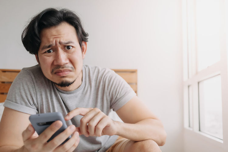 Portrait of man using mobile phone at home
