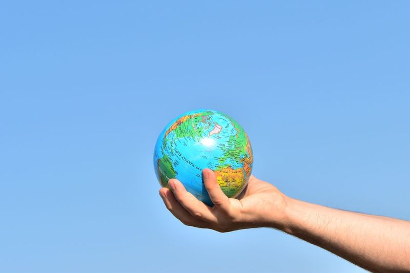 Cropped hand of man holding globe against clear blue sky