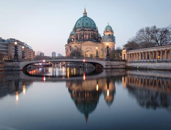 Reflection of illuminated bridge over river in city