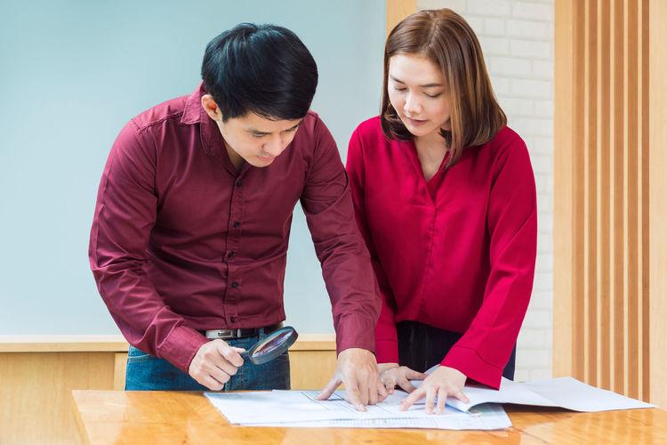 Two business man and woman checking the work on their blueprint during their meeting Architecture Checking In Meeting Planning Blueprint Business Document Inspecting Looking Down Paperwork People Secretary Table Two People
