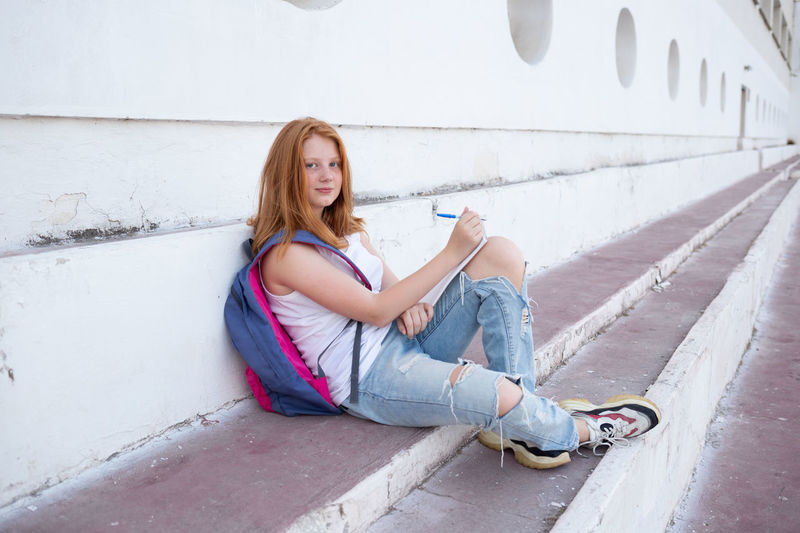 Portrait of young woman sitting against wall