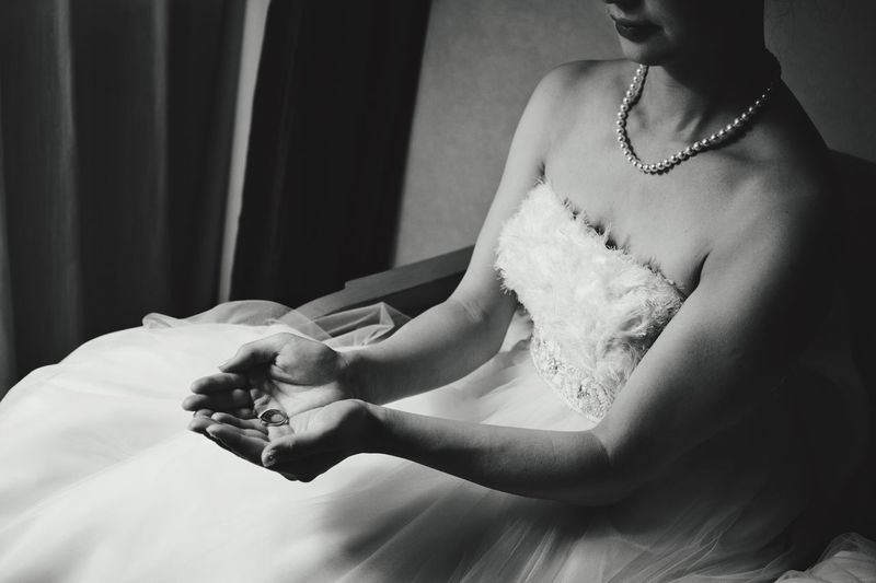 Midsection Of Bride Wearing Wedding Dress Holding Ring While Sitting On Chair